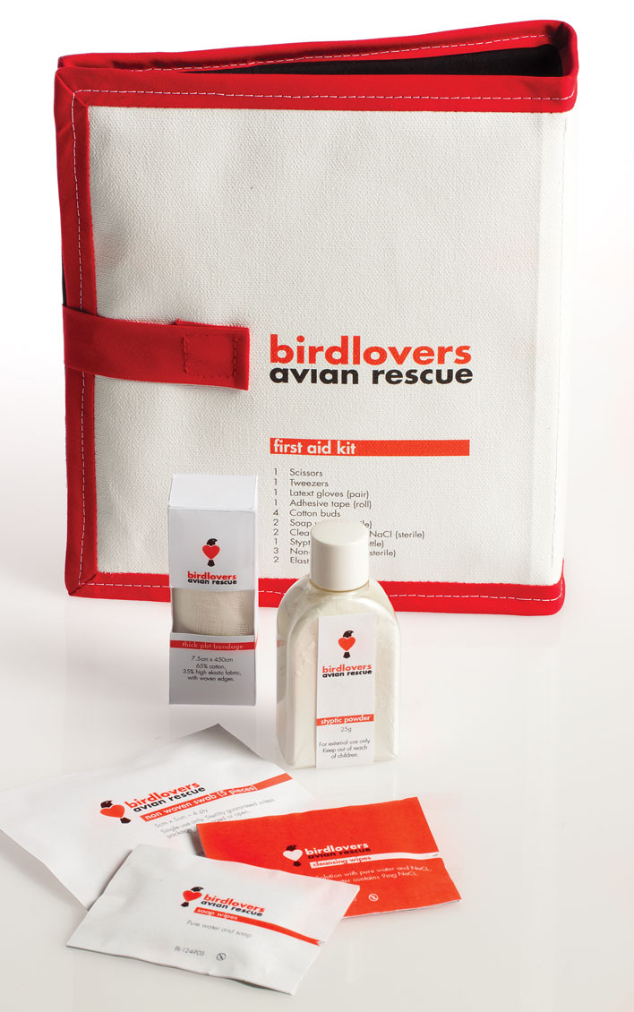 The first-aid kit for Birdlovers Avian Rescue - a canvas wallet, with red trim and printed with the brand's logo. In front of the first-aid kit sits some of the contents including packaged bandages, a bottle of styptic powder, swabs and cleansing wipes all packaged with the brand's logo and colours in black, white and red.