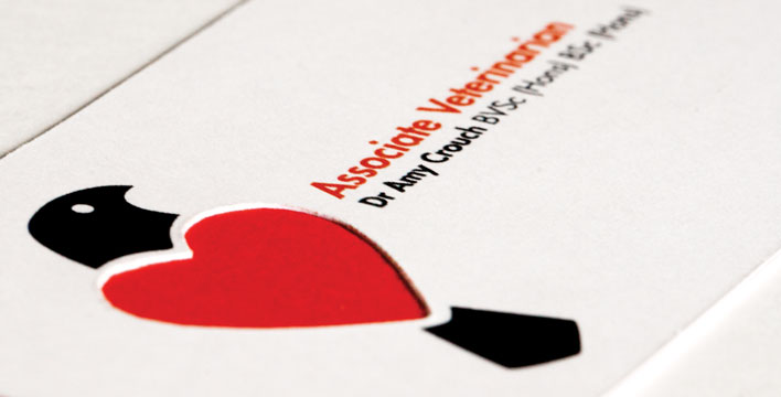 The business card is layered with a thin red paper sandwiched between two white cards. The card back features the logo's bird element with heart-shaped wings cut out to reveal the red layer.