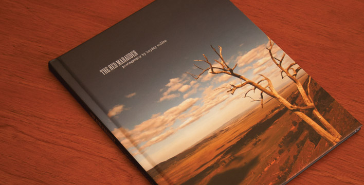 The cover of the hard-back photography book Red Marauder, featuring original photography. The cover photo was taken overlooking the near-empty Lake George, just outside of Canberra.